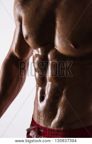 Focus on stomach. Dark contrast shot of young muscular fitness man stomach and arm. Bodybuilder with beads of sweat training in gym.
