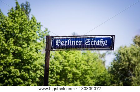 German road sign Berliner Strasse in front of trees