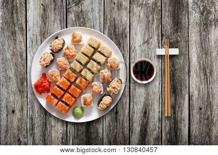 Japanese food restaurant, sushi maki gunkan roll plate or platter set. Chopsticks, ginger and wasabi. Sushi at white round plate, rustic wood background. Top view with soy sauce