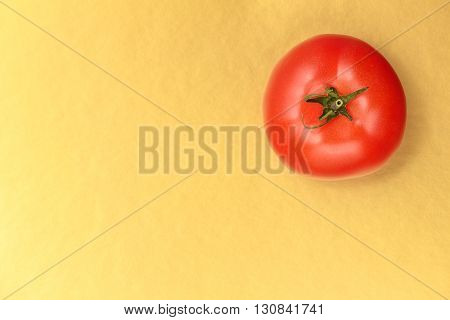 Top view of a red juicy tomato on a gold background. Bright and juicy tomato in the top right corner of the image. Tasty tomato. Tomato wallpaper. Tomato menu. Tomato poster. Vegetable texture