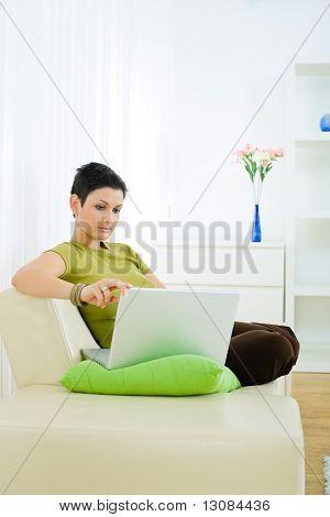 Joven trabajando en la computadora portátil en casa.