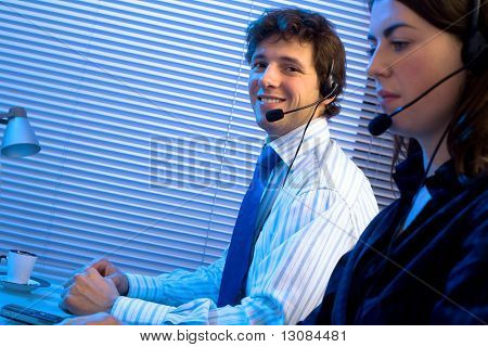 Customer service team working in headsets, late night at office. Focus placed on smiling man in back.