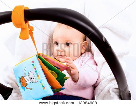 Baby playing with story book sitting in baby carrier.