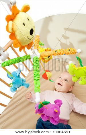 Happy baby playing with bed side toy, smiling.