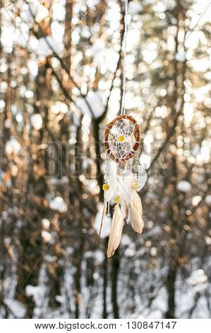 Handmade colorfull dream catcher in the snowy forest. Tribal elements owl feathers