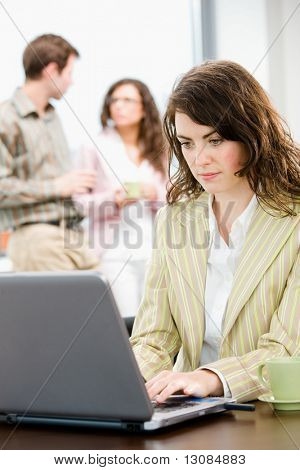 Team of young successful business people talking and drinking coffee at office, businesswoman working on laptop computer in front.