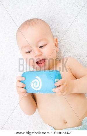 Happy Baby junge (1 Jahr alt) am Boden zu Hause liegen und spielen mit Stofftier. Spielzeug ist Eigenschaft rele
