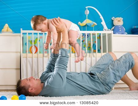 Father lying on back and lifting baby boy ( 1 year old ) at home in children's room.