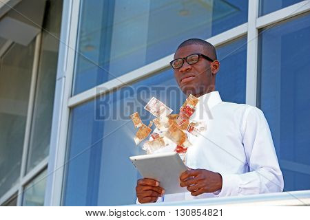 Financial concept. Make money on the Internet. Handsome African American businessman with digital tablet near business centre