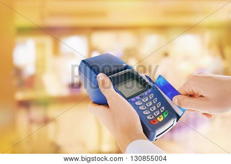 Credit card payment. Businessman using payment terminal on blurred background