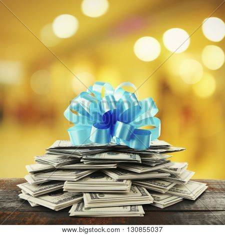 Pile of dollars with bow as gift on bright background