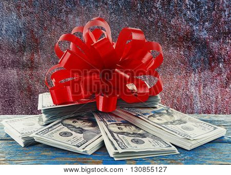 Pile of dollars with bow as gift