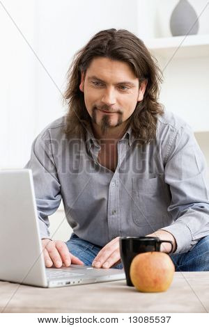 Casual man using laptop computer at home, smiling and looking at screen.