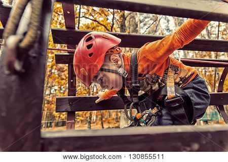 Portrait of 3 years old boy wearing helmet and climbing. Child in a wooden abstacle course in adventure playground