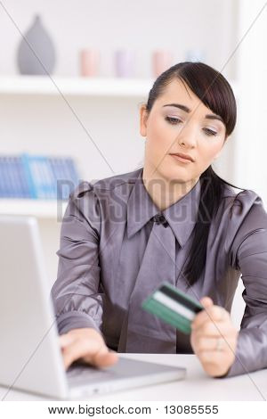 Young women shopping online at home, using laptop computer, holding credit card in hand.