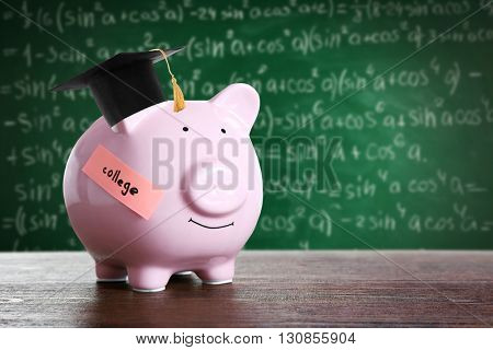Piggy bank with black graduate hat on blackboard background. Money for college concept