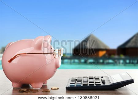 Pink piggy bank with glasses and calculator on resort background