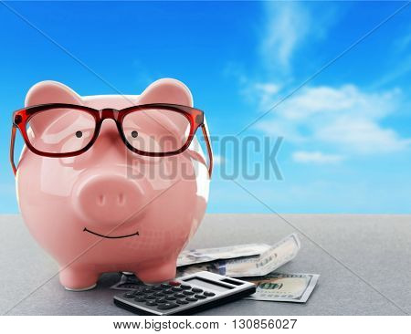 Pink piggy bank with dollar banknotes, glasses and calculator on sky background
