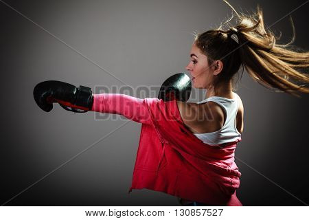 Martial arts or self defence concept. Sport boxer woman in black gloves. Fitness girl training kick boxing.