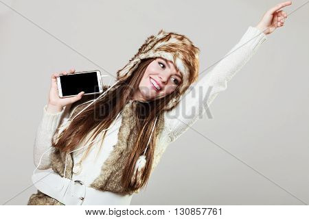 Winter girl listening music using phone with headphones raising hand. Happy woman wearing fur vest and warm hat in freezing cold time having fun posing.