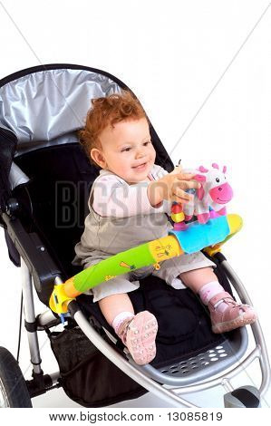 One year old red haired baby girl with baby stroller. Studio Shot. All toys visible on the photo are officialy property released.