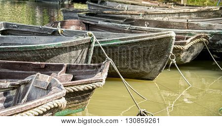 Empty old wooden boats on the murky river