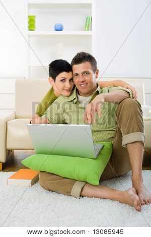Young couple browing internet at home on laptop computer, sitting on floor and lying on couch, embracing.