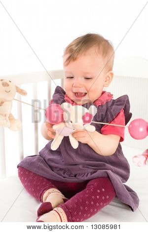 Cute baby girl (1 year old) sitting on crib, holding soft toys. Isolated on white, smiling. Toys are offically property released.