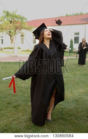 A beautiful graduate girl in the mantle keeps in hands graduate diploma and looks up.