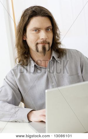 Portrait of casual businessman working at desk using laptop computer, looking at camera, smiling.