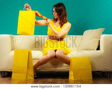 Buying retail sale concept. Fashionable girl summer dress high heels sitting on couch with shopping bags on green