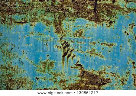 Blue aged metal wall with corrosion in close-up