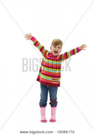 Happy little girl in colorful sweater, jeans and pink boots, laughing and waving. Isolated on white background.