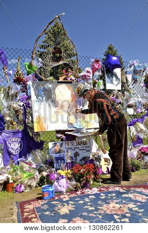 CHANHASSEN, MINNESOTA, May 13, 2016: Memorials of flowers, balloons, and purple decorate the fence around Paisley Park, the home of Prince Rogers Nelson as an unknown artists does a portrait of the musician
