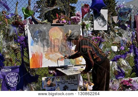 CHANHASSEN, MINNESOTA, May 13, 2016: Memorials of flowers, balloons, and purple decorate the fence around Paisley Park, the home of Prince Rogers Nelson as an unknown artist paints a portrait of the musician.