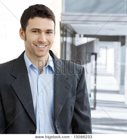Portrait of successful young businessman at corporate location.