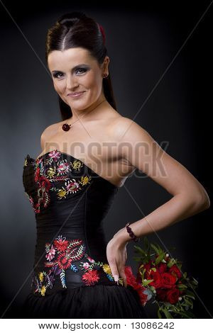 Beautiful young woman posing in a black cocktail dress holding a bouqet of red roses, looking flirtatious.