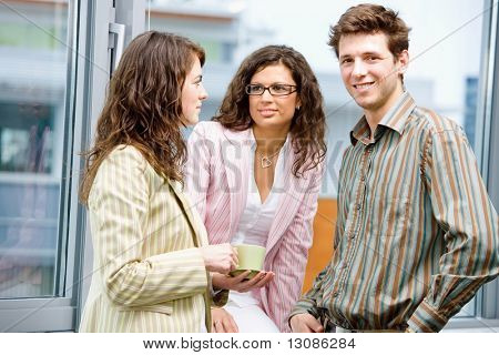 Happy young business people drinking coffe and talking at office in front of window, smiling.