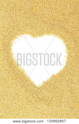 Raw uncooked amaranth seeds heap heart shaped on white background with copy space