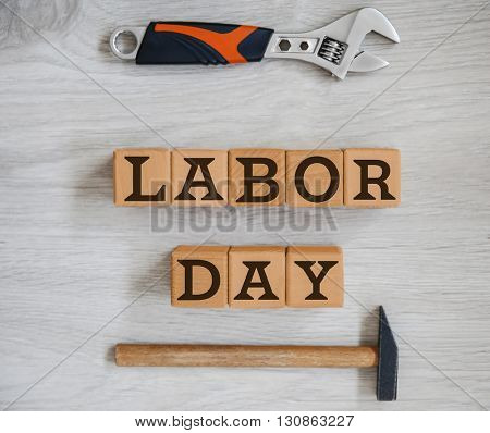 Construction tools and wooden cubes with text LABOR DAY on wooden background