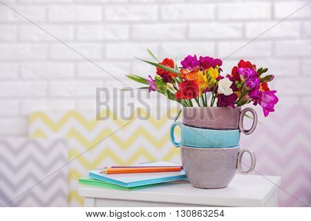 Beautiful freesia flowers on wooden stool on white brick wall background