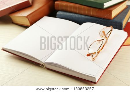 Blank open book with glasses on table