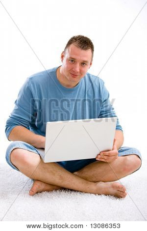 Young casual man sitting on floor using laptop computer. Isolated on white.