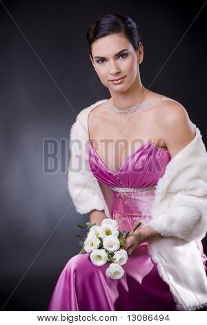 Beautiful young woman sitting on a chair wearing purple evening dress with white fur stole, holding bouqet of white roses.