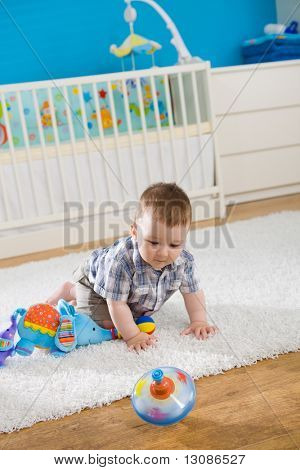 Baby boy ( 1 year old ) sitting on floor at home and playing with whirligig.