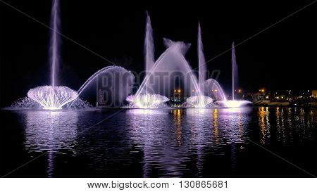 Fountain with bright illumination on the water pond or river with beautiful reflection at the evening or night. Beauty and calm tranquility urban recreational concept.