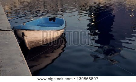 Boat at the quay moorage at sunset reflecting in water in the evening twilight dusk. Summer warm and calm concept.