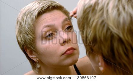 Blond short hair woman plucks and pulls her eyebrows out in front of mirror. Beauty and makeup concept.