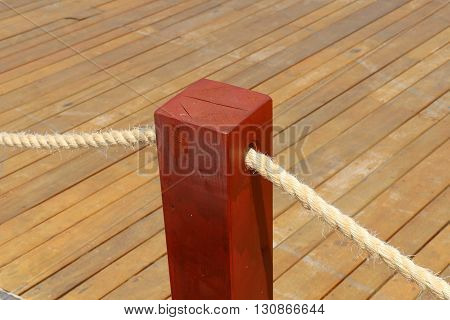 through a short wooden pole stretched thick rope