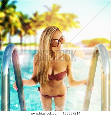 Woman rising from the outdoor pool ladder